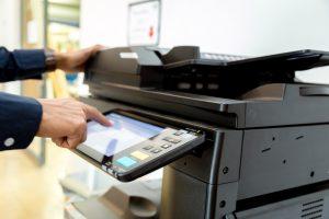 Hand press button on panel of printer, printer scanner laser office copy machine supplies start concept.
